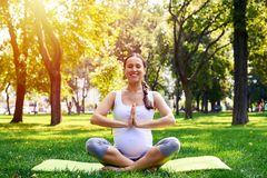 做瑜伽锻炼的迷人的孕妇在公园 免版税库存照片