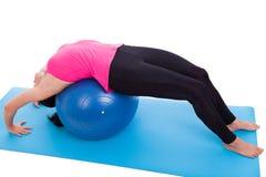 做瑜伽,在健身房球的谎言的妇女 库存图片