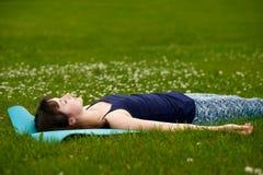 做瑜伽,思考, Shavasana或者尸体位置的女孩在公园在绿草 库存图片