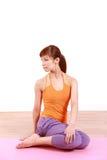 做瑜伽贤哲转弯的年轻日本妇女 免版税库存图片