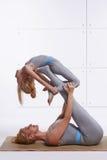做瑜伽锻炼健身健身房的母亲女儿佩带同样舒适的田径服家庭体育配对了在后面锂的妇女谎言 免版税图库摄影
