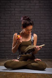 做瑜伽锻炼和读的书的美丽的女孩 免版税图库摄影