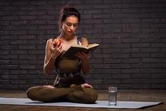 做瑜伽锻炼和读的书的美丽的女孩 免版税库存图片
