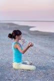 做瑜伽锻炼在海的背景的美丽的青少年的女孩莲花姿势在日落, 库存照片