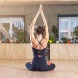 做瑜伽锻炼思考的坐在与被举的胳膊的莲花姿势的亭亭玉立的妇女背面图  免版税图库摄影