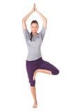 做瑜伽锻炼树姿势的少妇被隔绝 免版税库存照片