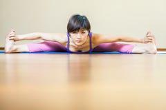 做瑜伽锻炼的亚裔妇女分裂室内 免版税库存图片