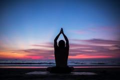 做瑜伽锻炼的人剪影在日落 免版税库存照片