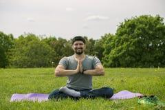 做瑜伽锻炼的人在公园 免版税图库摄影