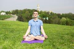 做瑜伽锻炼的人在公园 库存照片