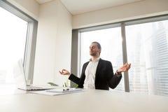 做瑜伽锻炼的商人在工作场所 免版税库存照片