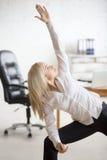 做瑜伽锻炼的女商人 免版税库存照片