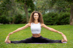 做瑜伽锻炼的微笑的俏丽的妇女 免版税库存图片