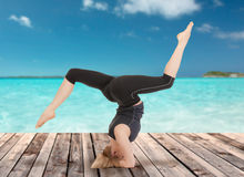 做瑜伽锻炼的愉快的少妇 免版税库存图片