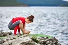 做瑜伽锻炼的美丽的妇女室外在岩石在河附近 免版税库存图片