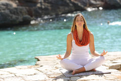 做瑜伽锻炼的轻松的女孩在度假 免版税库存照片