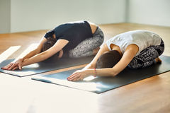 做瑜伽asana儿童的姿势的两个少妇 库存照片