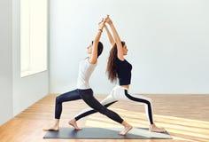 做瑜伽asana战士一姿势的两个少妇 图库摄影