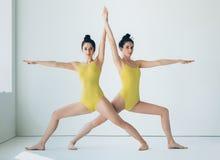 做瑜伽asana战士II姿势的两个少妇 库存照片