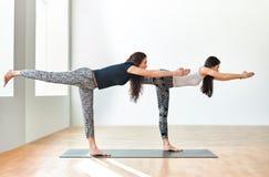 做瑜伽asana战士III姿势的两个少妇 库存照片