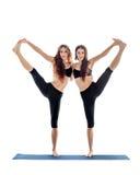 做瑜伽asana的两个少妇对大脚趾姿势伸出了手 免版税库存图片