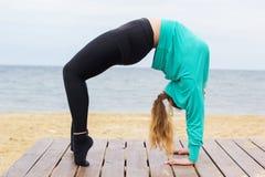 做瑜伽asana的嬉戏肥满妇女在海附近 免版税库存图片