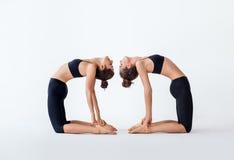 做瑜伽asana骆驼姿势的两个少妇 免版税库存照片