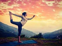 做瑜伽asana Natarajasana的妇女户外在瀑布 免版税库存图片
