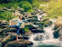 做瑜伽asana Natarajasana的妇女户外在瀑布 库存图片