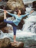做瑜伽asana Natarajasana的妇女户外在瀑布 免版税库存照片
