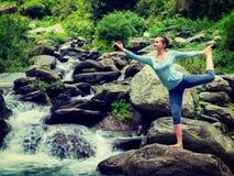 做瑜伽asana Natarajasana的妇女户外在瀑布 免版税图库摄影