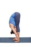 做瑜伽asana Uttanasana -站立的向前弯的妇女 免版税库存照片