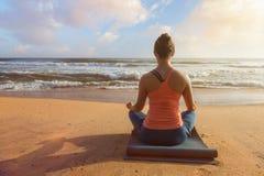 做瑜伽oudoors在海滩- Padmasana莲花姿势的妇女 免版税库存照片