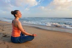 做瑜伽oudoors在海滩- Padmasana莲花姿势的妇女 免版税库存图片