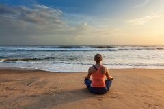做瑜伽oudoors在海滩- Padmasana莲花姿势的妇女 库存照片
