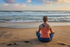 做瑜伽oudoors在海滩- Padmasana莲花姿势的妇女 库存图片