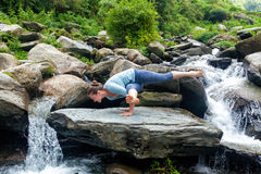 做瑜伽oudoors的年轻人适合的妇女在瀑布 免版税库存图片