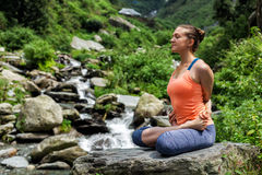 做瑜伽oudoors的年轻人适合的妇女在瀑布 免版税库存照片