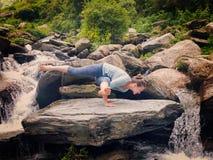 做瑜伽oudoors的年轻运动的适合妇女在热带瀑布 库存图片