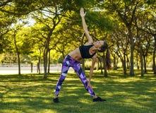 做瑜伽trikonasana姿势的女孩在公园 免版税图库摄影