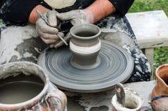 做瓦器的手特写镜头由黏土在轮子。 免版税库存照片