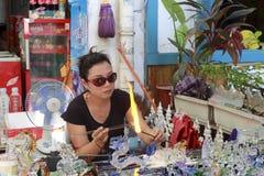 做瓶的女性玻璃艺术家示范由一块熔融态玻璃 免版税图库摄影
