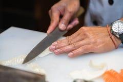 做生鱼片的厨师在厨房里 图库摄影