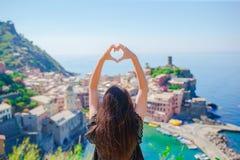 做用手心脏形状的美丽的女孩在韦尔纳扎,五乡地老沿海城市背景国家公园 免版税库存照片