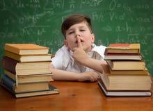 做用手指标志沈默的男小学生 免版税库存照片