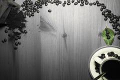 做用老葡萄酒减速火箭的研磨机的咖啡链子用碾碎的咖啡和杯子与咖啡豆绿色叶子的无奶咖啡 库存照片
