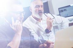做电话会议的小组两个伙伴在现代办公室谈论一个新的企业想法 年轻有胡子的商人 免版税库存照片