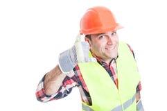 做电话姿态的英俊的建造者 库存照片
