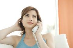 做电话微笑的妇女的购买权 库存图片