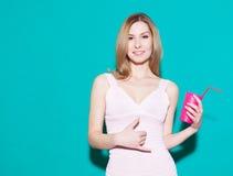 做电话我标志和微笑在有玻璃的桃红色礼服的少妇在她的手上 绿色backgrounde在演播室 免版税图库摄影